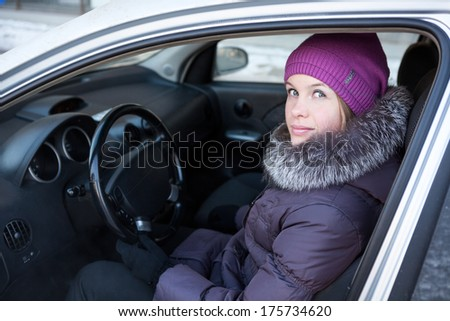 Woman in winter clothes sitting in his car - stock photo