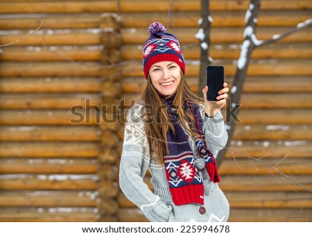 Woman in winter clothing using mobile phone. focus on face - stock photo