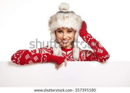 Woman in winter dress holding a blank billboard, white background, copyspace  - stock photo