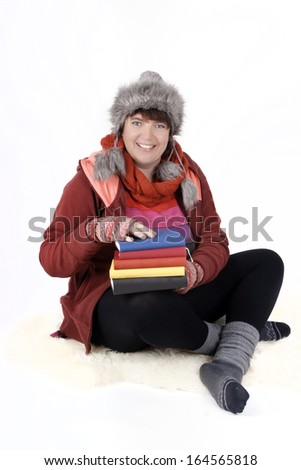 Woman in winterclothes holding a stack of books - stock photo