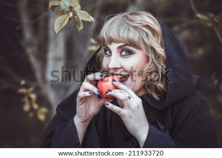 Woman in witch costume with red apple in wood - stock photo
