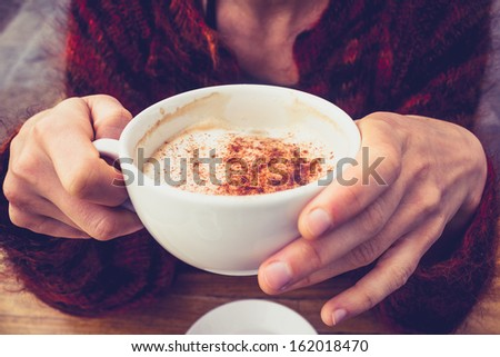 Woman in wool jumper drinking coffee on cold day - stock photo