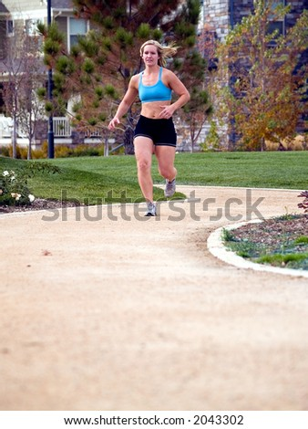 Woman in workout clothing jogging on a suburban path.