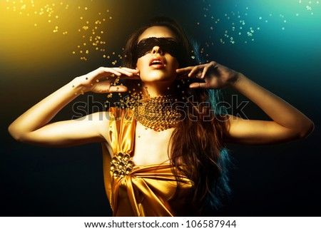 woman in yellow dress and mask with jewelry - stock photo