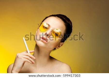 woman in yellow glasses on yellow background With a cigarette in hand