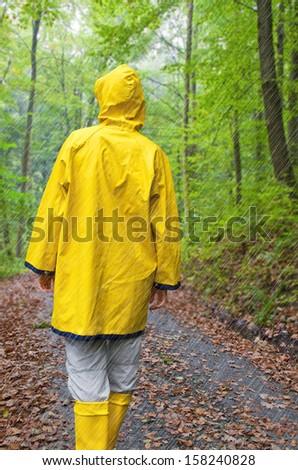 Woman in yellow raincoat walking in rain - stock photo