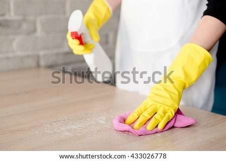 Woman in yellow rubber gloves cleaning table with pink cloth - stock photo