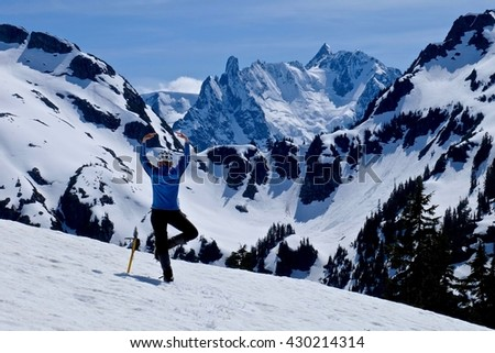 Woman in Yoga Pose Meditating and Enjoying Snow Covered Mountain View.  Ruth Mountain, North Cascades National Park, Seattle, Washington State, USA - stock photo