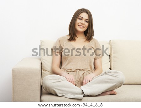 woman in yoga pose on sofa at home. relaxing portrait of beautiful girl
