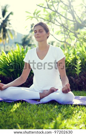 Woman in yoga poses in the tropical garden - stock photo