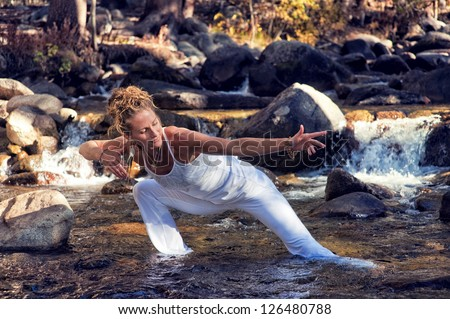 Woman in yoga posture outdoors in a forest river.