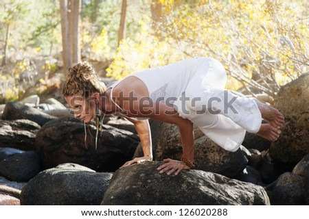Woman in yoga posture outdoors in the forest. - stock photo