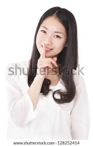 Woman index finger against the mouth - stock photo