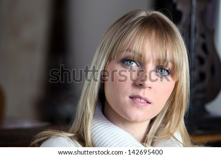 Woman indoors in a winter jumper - stock photo