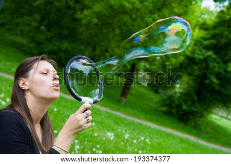 woman inflating colorful soap bubbles in spring park