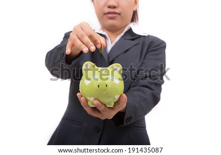 Woman Inserting Coin In Piggy bank