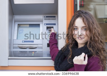woman inserting credit card to ATM - stock photo