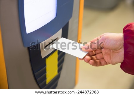 Woman Inserting Ticket Into Machine To Pay For Parking - stock photo