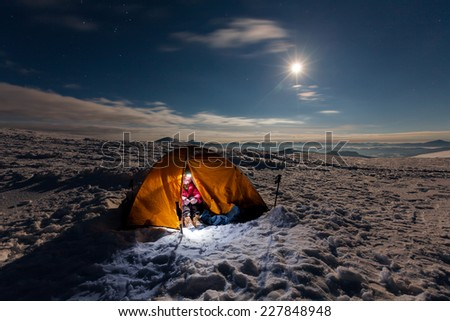 Woman inside tent during winter night - stock photo