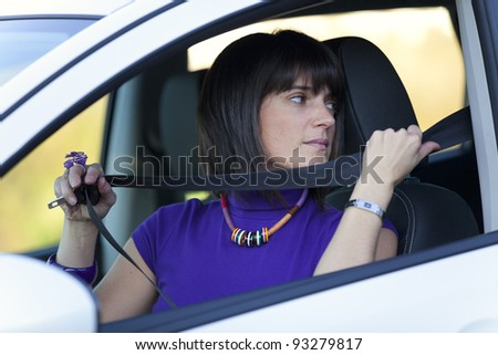 Woman inside the car putting her safety belt