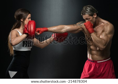 Woman Instructor And Man Training Mixed Martial Art - Bodybuilding Couple Posing With Boxing Gloves On Black Background - stock photo