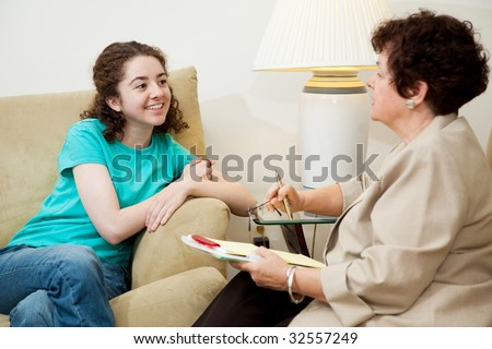 Woman interviewing a teen girl for college admission or job.  Could also be counseling session. - stock photo