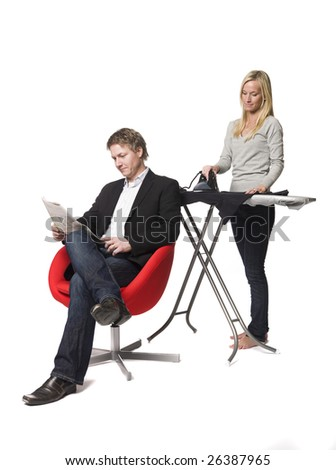 Woman ironing and the man reading a paper - stock photo