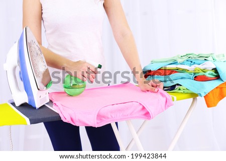 Woman ironing clothes on ironing board, close-up, on light background - stock photo