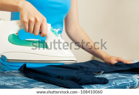 Woman ironing her clothes - stock photo