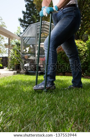 Woman is aerating lawn by manual aerator in back yard