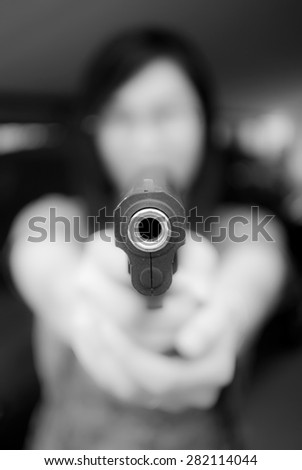 Woman is aiming gun to the photographer by blurry black and white style.