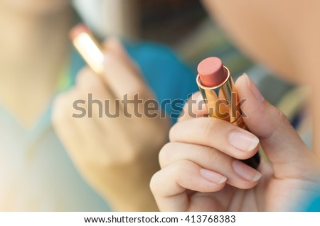 Woman is applying makeup and looking in the mirror. Close up of red lipstick. Woman hand is holding lipstick.