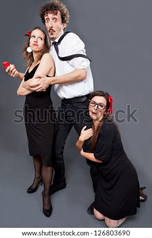 Woman is begging a man not to leave her while he courts another woman - stock photo