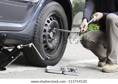 Woman is changing  tire with wheel wrench.