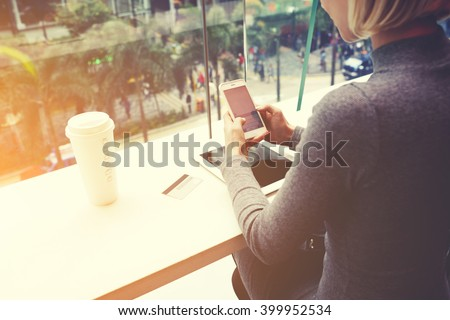 Woman is chatting on mobile phone, while is sitting in cafe at the table with digital tablet, credit card and take away coffee. Female is booking restaurant for dinner on-line via cell telephone - stock photo
