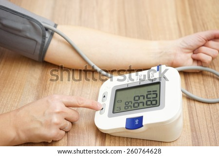 Woman is checking blood pressure at home - stock photo