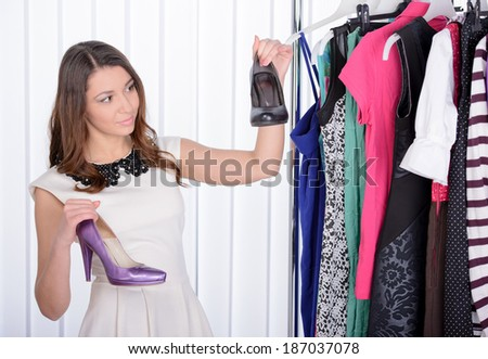 Woman is choosing shoes . She stands near her clothes rack with lots of dresses - stock photo