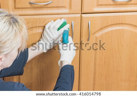 Woman is cleaning the furniture with a sponge and detergent, which she is holding in her hands. All potential trademarks are removed. - stock photo