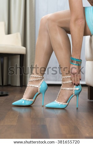 woman is closing the ankle straps of her high heels shoes.