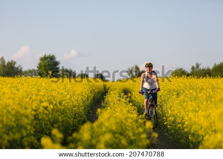 Woman is cycling in yellow rapeseed field - stock photo