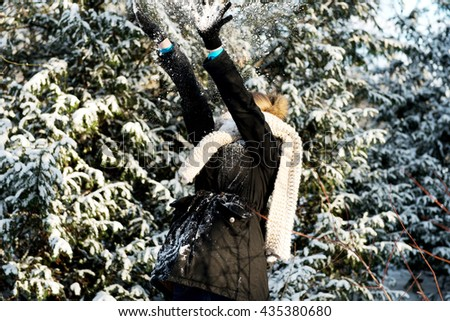 Woman is defending herself playing snowball fight - stock photo