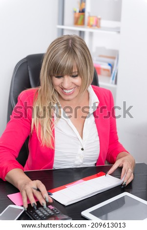 Woman is doing calculations with a desk calculator while sitting at the desk in the office. The woman is looking down.