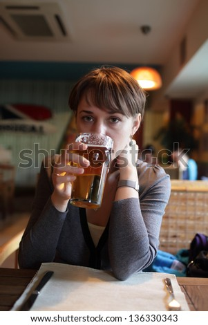 Woman is drinking beer in a pub
