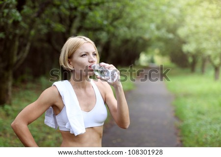 Woman is drinking water after exercising. Jogging in the park.