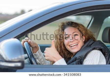 woman is driving her car and giving a thumb up gesture