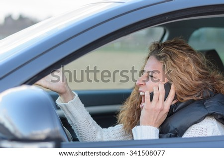 woman is driving her car very aggressive and having a call