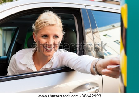 Woman is driving into a parking garage and is slipping the ticket into the barrier of the garage - stock photo