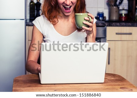 Woman is excited about her laptop - stock photo