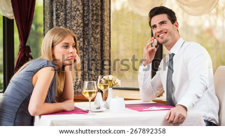 Woman is getting bored in restaurant while her boyfriend is talking on the phone - stock photo