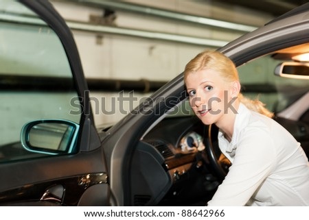 woman is getting into her car in the parking garage - stock photo